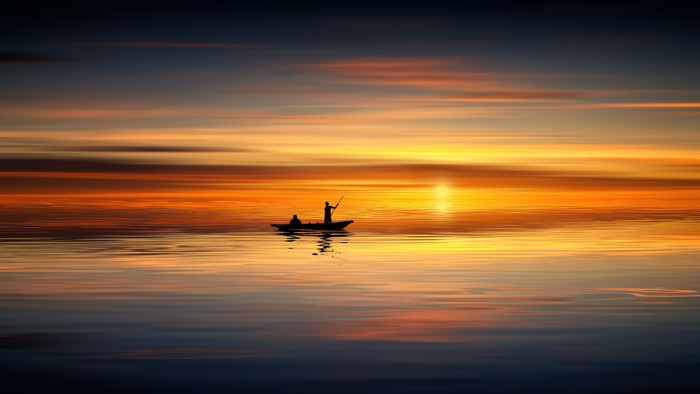 The silhouette of men in a boat at sunset