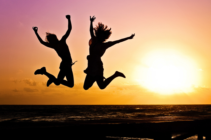 The silhouette of two girls jumping over the sea at sunset