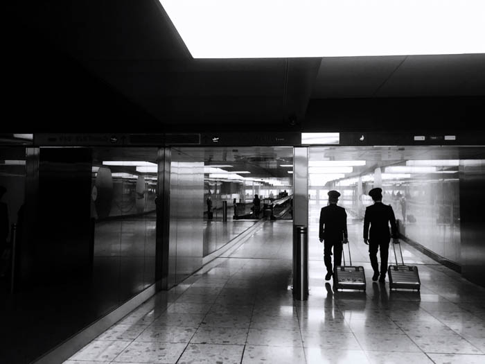 Candid shot of two pilots in an airport corridor. Black and white retro style image showing a back view of the pilots with their luggage, heading towards their flight.