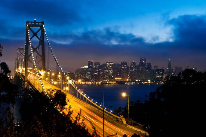 Uma imagem da Bay Bridge e a vista do centro de São Francisco à noite
