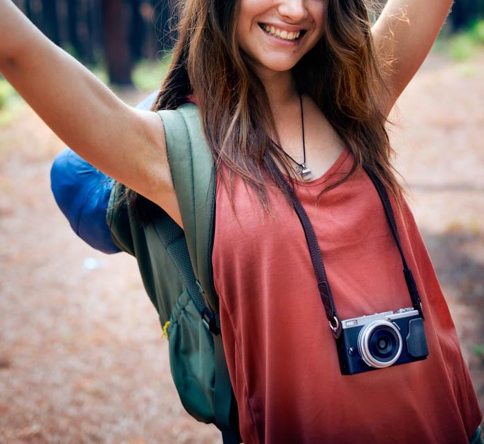 Um jovem fotógrafo de viagens posando com sua câmera