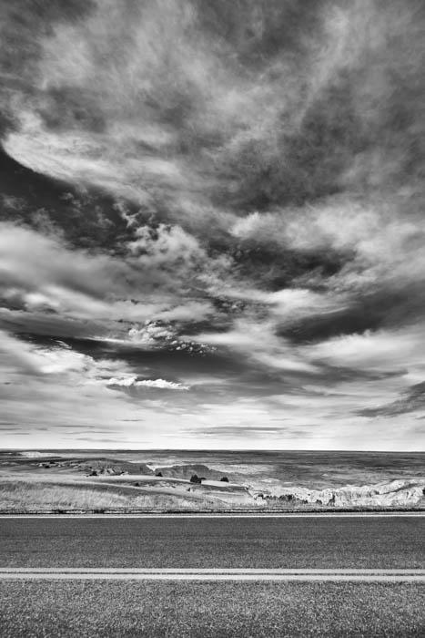 Uma fotografia preto e branco de uma estrada e nuvens.