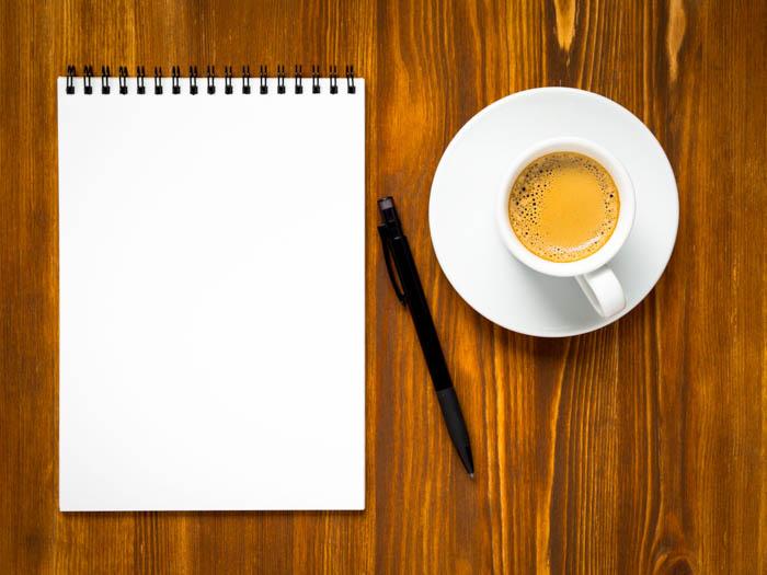 Abra o bloco de notas com uma página em branco para escrever uma lista de tarefas de viagens, uma xícara de café e uma caneta na mesa de madeira marrom