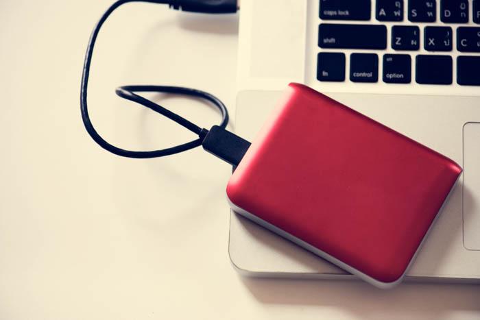Um disco rígido externo colocado em um laptop.