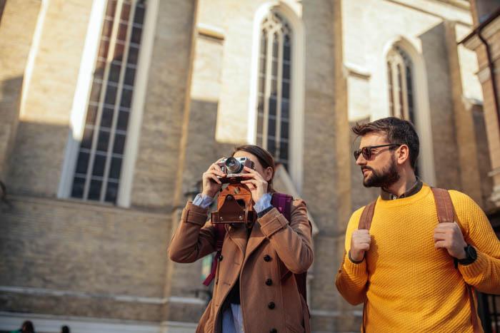 Uma fotógrafa de viagens tirando uma foto arquitetônica com o namorado
