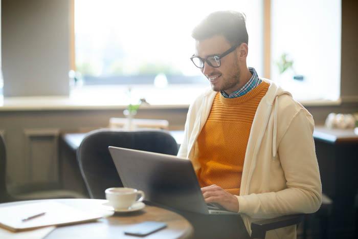 Blogueiro de fotografia feliz com laptop
