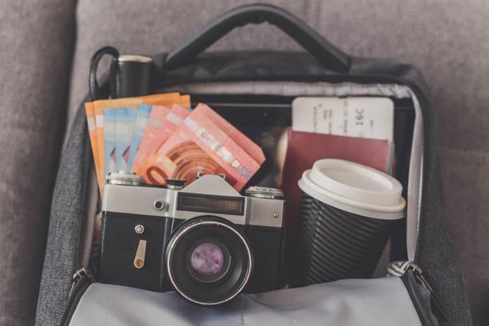 Mochila aberta com coisas necessárias para fotografia de viagem, como câmera, dinheiro, passaporte e passagens