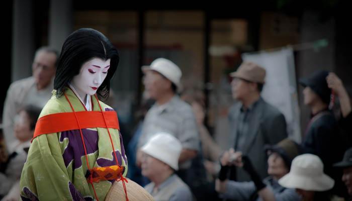 Uma foto de rua de uma mulher japonesa em trajes de gueixa
