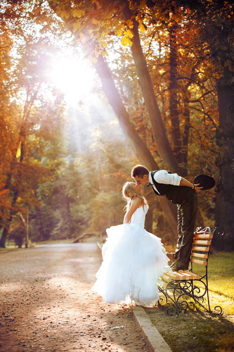 Atypical image of the groom standing up on a bench while giving a kiss to the bride