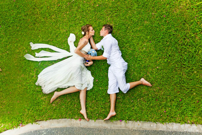 Couple laying on a green grass while imitating a jump shot from flat lay angle