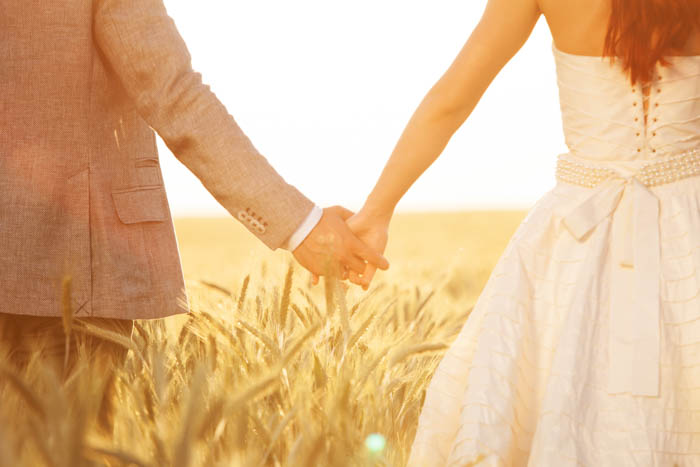 A picture of a bride and groom holding each other's hand