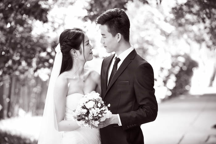 Outdoor portrait of asian bride and groom, happy and smiling, black and white.