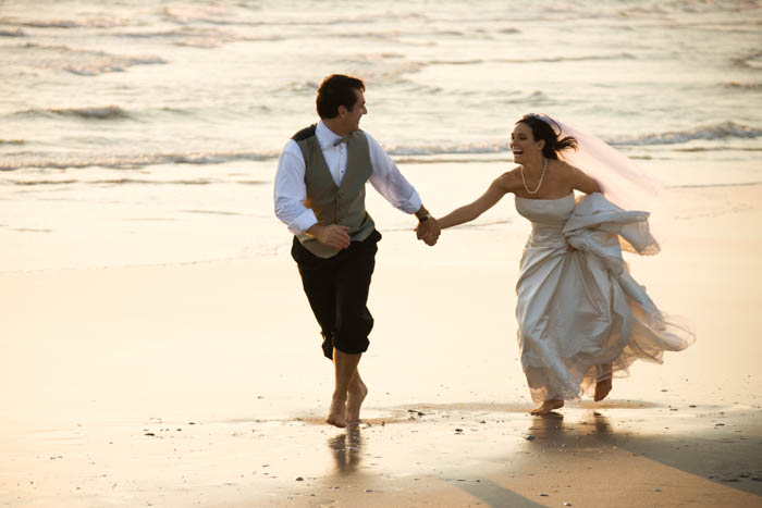 An image of the groom and the bride running at the beach