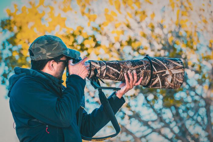 Um fotógrafo segurando uma lente telefoto na natureza.