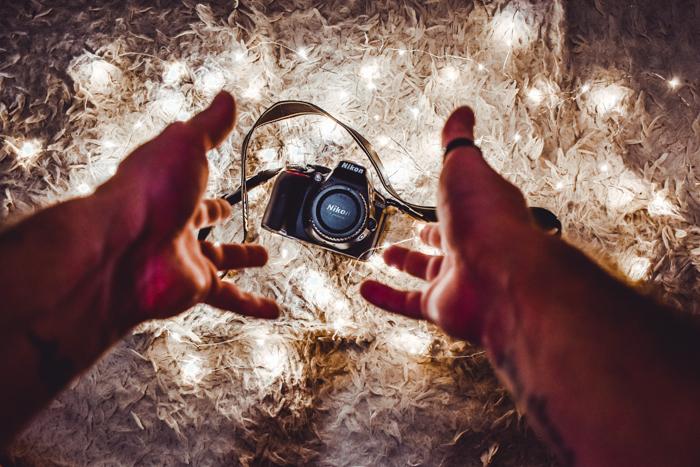 Mão jogando uma câmera DSLR Nikon