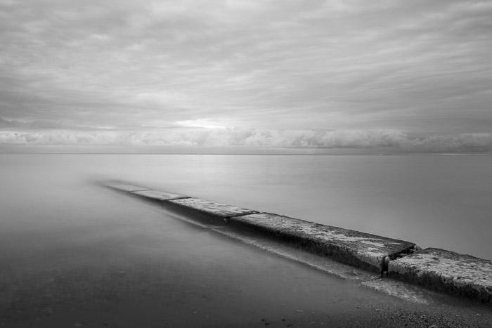 Fotografia de longa exposição da barreira estendendo-se para a água ao nascer do sol monocromática