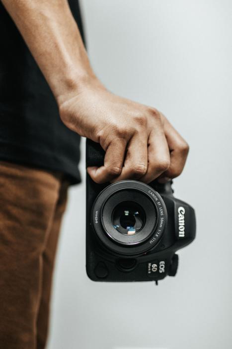 Homem segurando câmera Canon