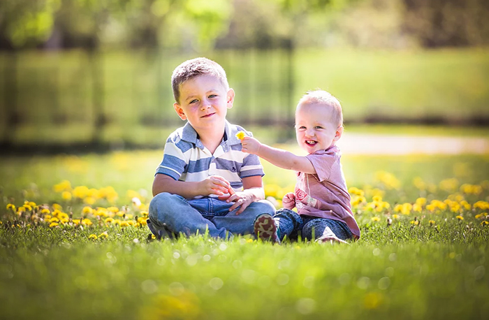 A photo of two happy child playing with each other in the grass.