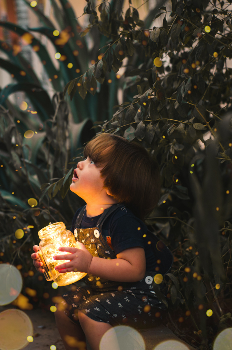A magical child photography of a little boy surrounded by fairy bokeh lights.