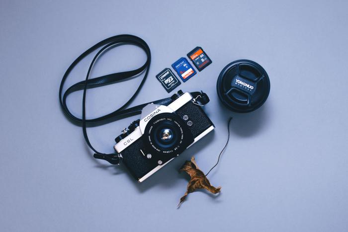 Uma câmera, vários cartões de memória e uma tampa de lente.
