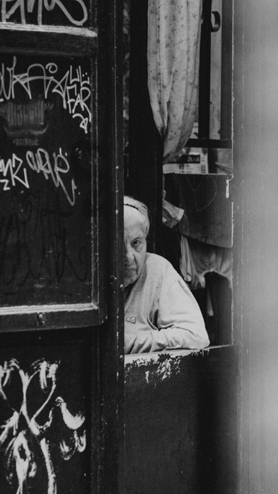 black and white image of an old person peeping at the camera
