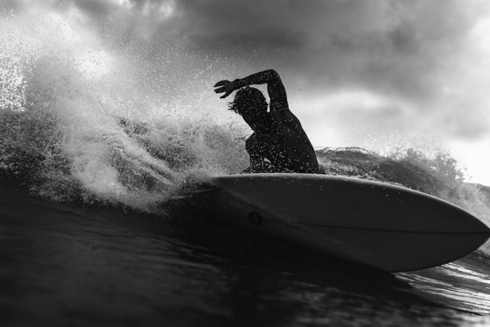 imagem em preto e branco de um homem com uma prancha de surf nas ondas