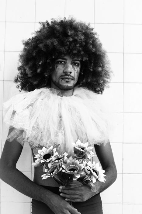 imagem estilística de uma pessoa afro segurando flores falsas