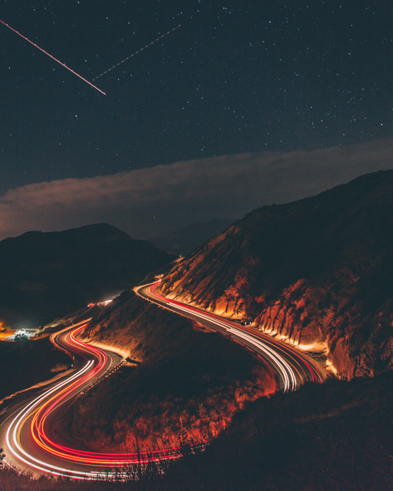 a time lapse photo of cars driving on a curved mountain road with shooting stars in the sky