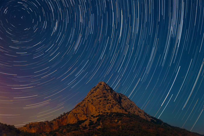 a time lapse image of the night sky behind a mountain