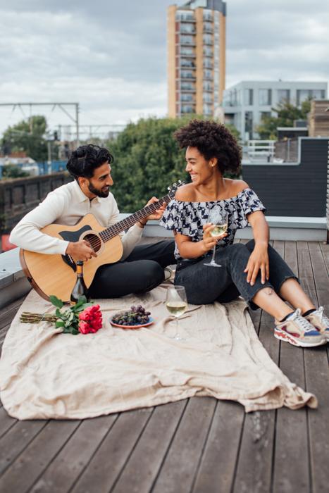 Imagem de um casal romântico fazendo um piquenique enquanto o noivo toca violão