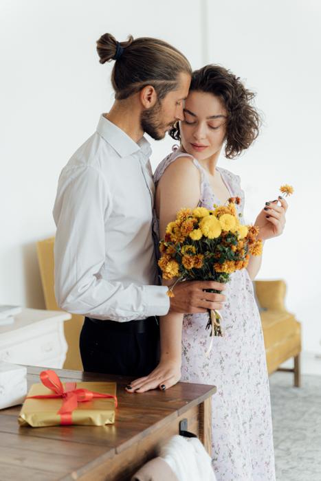 Uma imagem íntima de um jovem casal enquanto o menino maneja um balde de flores na garota por trás.