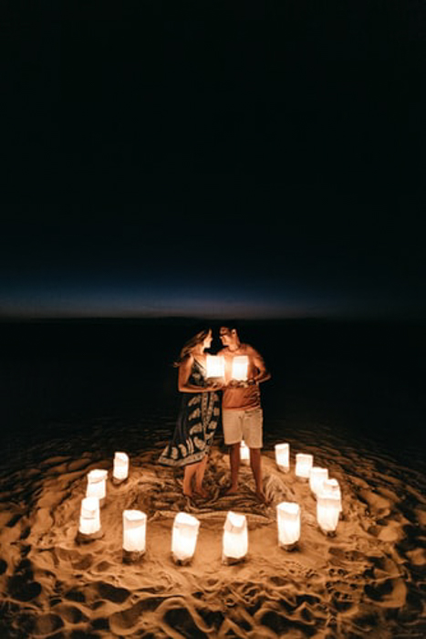 happy couple standing on the beach, surrounded by lanterns
