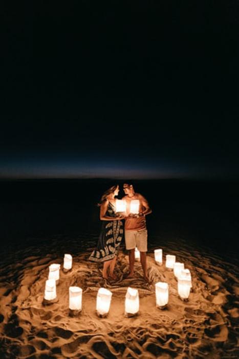 casal feliz em pé na praia cercado de lanternas