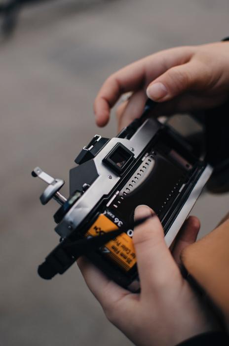 Um homem carregando um rolo de filme 35mm em sua câmera analógica