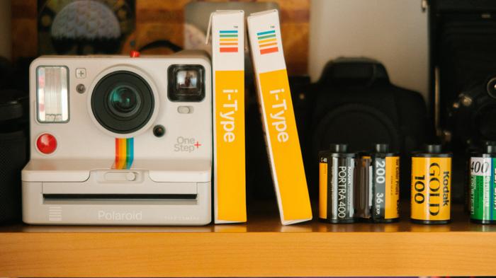 Uma imagem de uma câmera instantânea Polaroid e filmes instantâneos, além de rolos de filme de 35 milhões