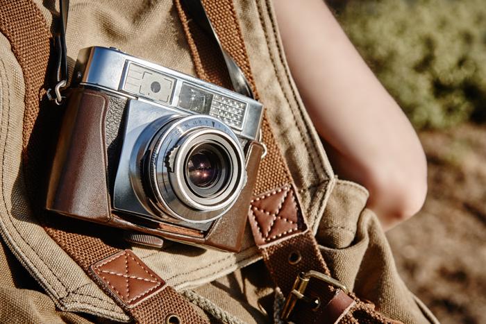 Uma imagem de uma câmera vintage em uma mochila de couro.