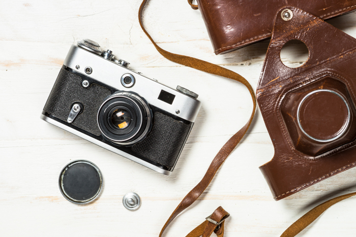 Uma câmera analógica vintage com um estojo de couro e seus acessórios em uma mesa