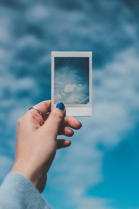Uma mão segurando uma foto de uma câmera instantânea