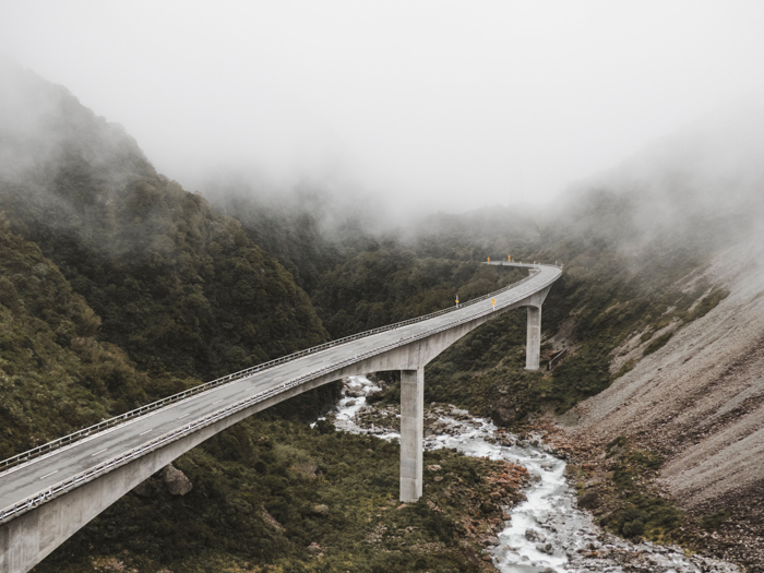 a photo of a road through mountains and fog show how to use leading lines photography