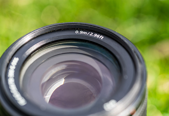 Lens showing minimum focusing distance numbers and letters