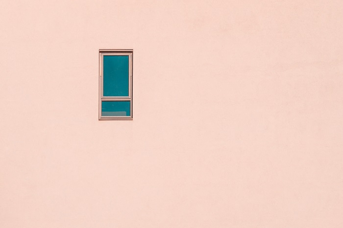 minimalist photography of a small window on a pink building facade