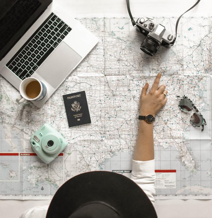 uma mulher apontando em um mapa com suas câmeras de viagem