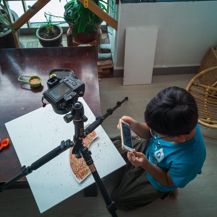 ένας άντρας που χρησιμοποιεί λευκή κάρτα κάτω από μια κάμερα για φωτογραφία στο σπίτι
