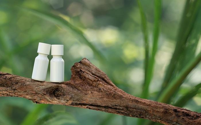 φωτογραφία προϊόντος δύο μπουκαλιών καλλυντικών σε κλαδί δέντρου