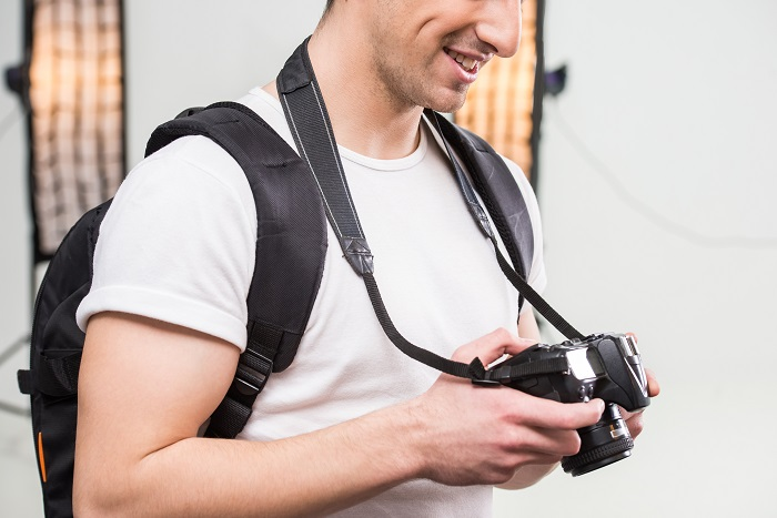 Young photographer with camera in professionally equipped studio is adjusting high speed sync flash on his DSLR camera