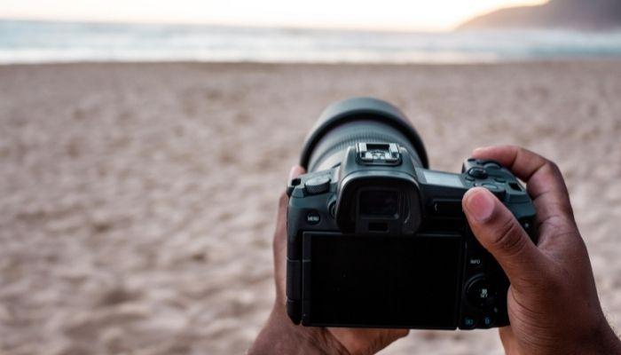 orang yang memegang kamera dslr di pantai