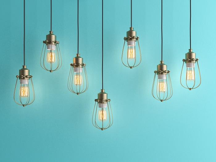 Sete lâmpadas vintage penduradas em um fundo azul.